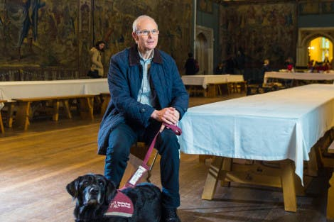 Male visitor in Great Hall sitting with guide dog at his feet
