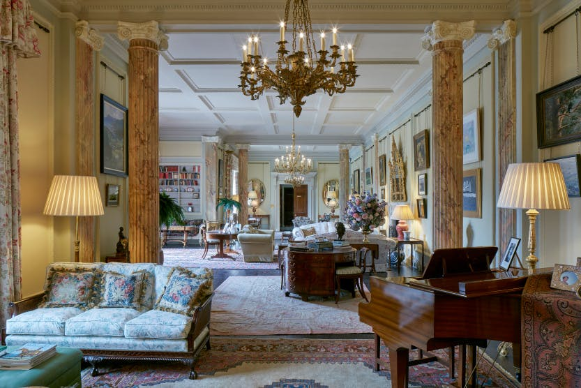 The State Drawing Room at Hillsborough Castle, design based on the inter-war feminine ideal of a country house drawing room, showcasing light neutral colours and paintings on the walls, as well as two marble columns.