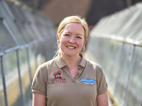 Female staff wearing uniform stands in between two glasshouses.