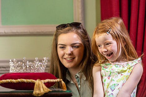 A young teenage girl and her younger sister smile as they view a replica of a silver tiara studded with diamonds, on a red display cushion.