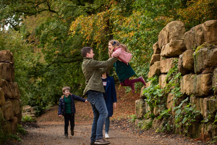 A family walk through the Lost Garden at Hillsborough Castle and Gardens in autumn 2019. A father is swinging his daughter up in the air as a mother and son watch.
