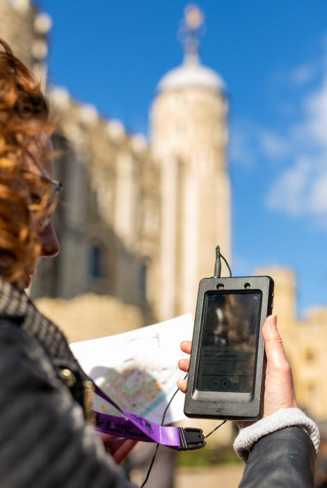 A visitor uses the audio guide outside the White Tower at the Tower of London.