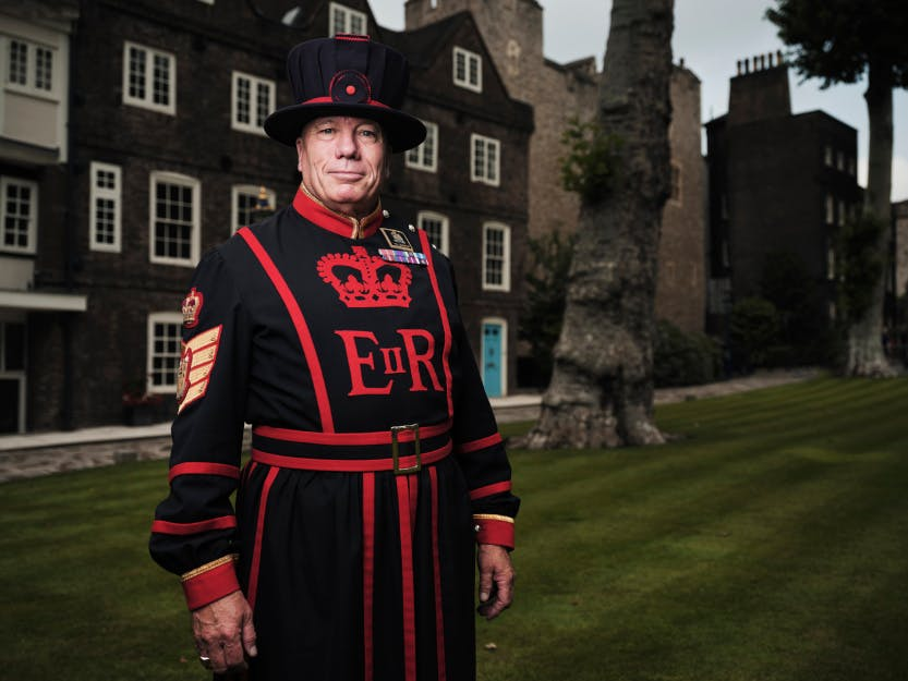 A Yeoman Warder, Yeoman Gaoler Bob Loughlin, stands on Tower Green in uniform surrounded by the Tudor buildings of the Tower of London