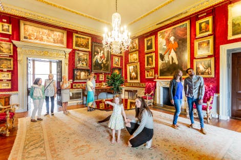 A group of visitors enjoying a viewing of the Red Room, one of Hillsborough Castle's State Rooms. Two young girls appear in the foreground along with a young couple. A small group of older ladies and gentlemen can be seen in the background having just entered the room. The walls are lined with a deep red silk damask and a variety of oil paintings in gold frames of various sizes fill the walls. A chandelier hangs above a small round wooden table in the centre of the room. The walls are lined with grey and gold detailing.