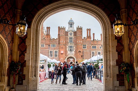 The Festive Fayre in Base Court at Hampton Court Palace. Large white tents cover the court and visitors can be seen looking at produce. The red-brick Tudor palace can be seen in the background.