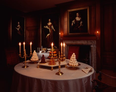 This room was used by King William III for small private dinner parties. The dining table is set with reproductions of gold plate and that King William III would have used. The third course of the meal, the dessert, is being served with pyramids of cherries, meringues and crystallised fruit