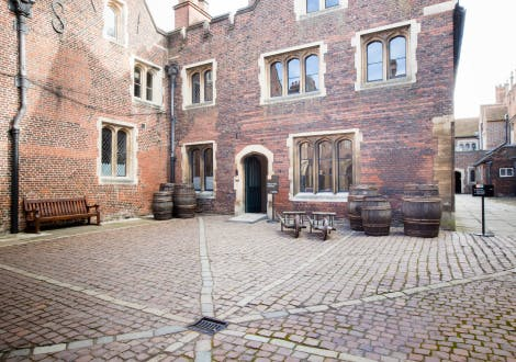Master Carpenter's Court, looking north-east towards the entrance to King Henry VIII's Kitchens. Wooden barrels stand on either side of the entrance to the kitchens.
