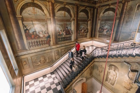 A guide talks to visitors on the King's Grand Staircase on a tour of the State Apartments at Kensington Palace