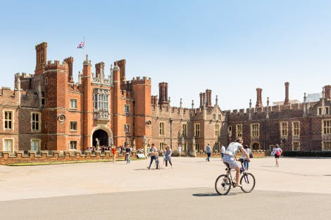 The West Gate of Hampton Court Palace, with visitors walking and cycling in front, under a blue sky