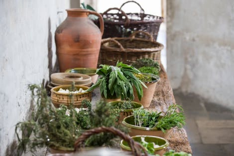 The Great Kitchens, looking east. Showing fresh herbs laid out on a wooden table. An earthenware jug and wicker baskets stand on the table in the background.