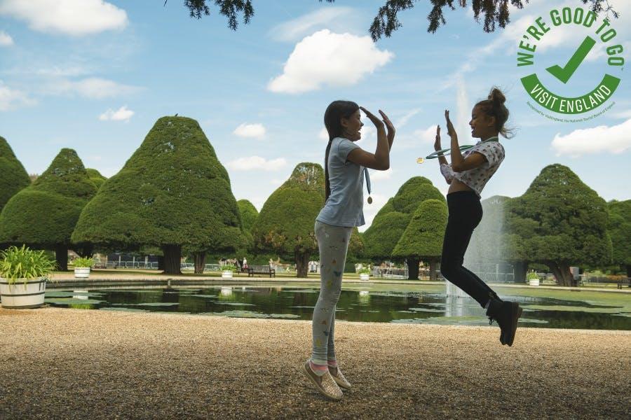Two girls jumping in Hampton Court Palace Great Fountain Garden