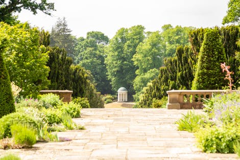 Lady Alice's Temple, looking west. The paved terrace is in the foreground.  This domed temple was given as a wedding gift to Lady Alice Hill by her brother, the 5th Marquess of Downshire in 1867. A circular seat inside the temple sits behind a screen of Ionic columns.