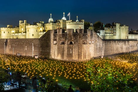 The Tower of London Moat, showing an aerial view of the Beyond the Deepening Shadow installation and lit-up city skyline